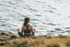 woman sits with her legs crossed facing the ocean