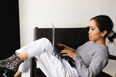 woman sits with her legs up and types on a laptop