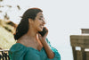woman smiles and holds a cellphone to her ear