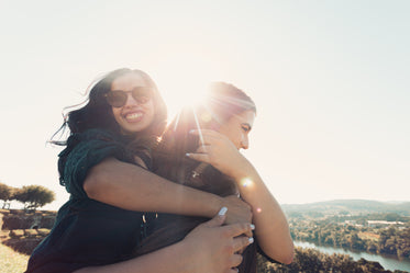 woman smiles and hugs a woman from behind