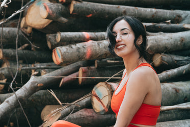 woman smiles at the camera while standing wood stack