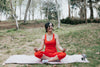 woman smiles while sitting in a yoga pose
