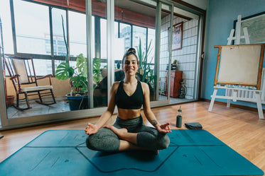 woman smiles wide sitting cross legged on yoga mat