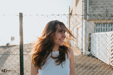 woman smiles wide standing in front of a fence