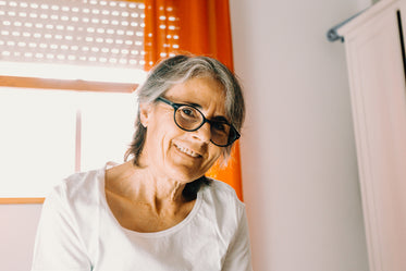 woman smiling to the camera with orange curtains behind