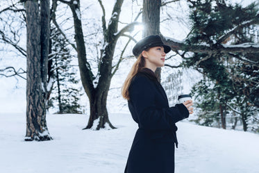 woman standing snowy wood
