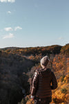 woman stands above fall colored valley