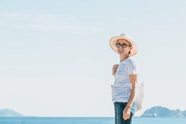 woman stands by open water and a straw hat
