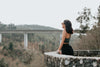 woman stands in at stone lookout and take in the forest view
