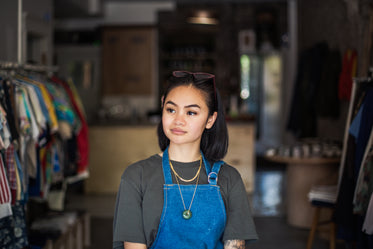 woman stands in store with apron on