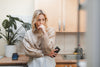woman stands in the kitchen with her hand close to her face