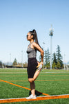 woman stretches her leg while standing on a sport field