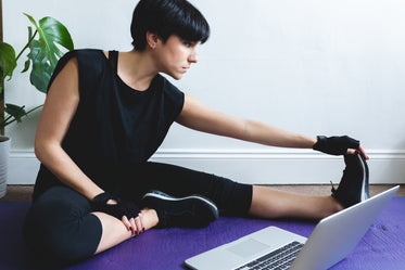 woman stretches while sitting in front of her laptop