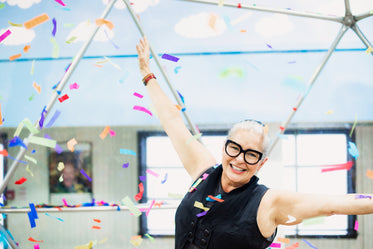 woman throws arms in air as rainbow confetti falls around her