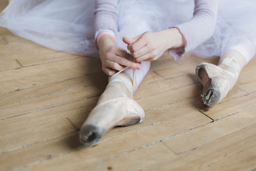 woman ties dance shoes