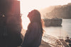 woman tilts her head back and closes her eyes at sunset