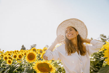 woman tilts her head up towards the sun holding onto hat