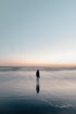 woman wades in ocean at sunset