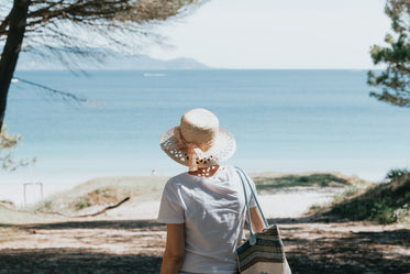 woman walks towards a beach and blue water