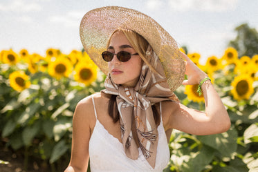 woman wearing a silk scarf stands in a field of sunflowers