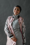 woman wearing headscarf in front of black background.