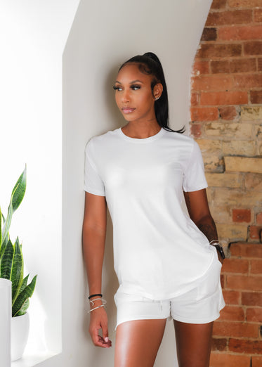 woman wears all white and leans in front of red brick wall