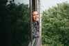 woman with a wide smile leaning out a window