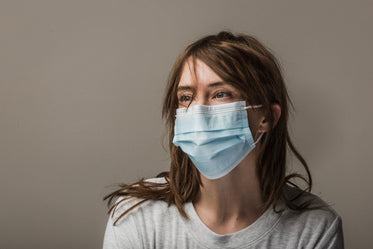 woman with brown hair wearing disposable face mask