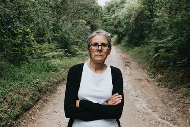 woman with her arms crossed on a tree lined trail