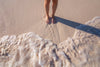 womans feet in sand with waves