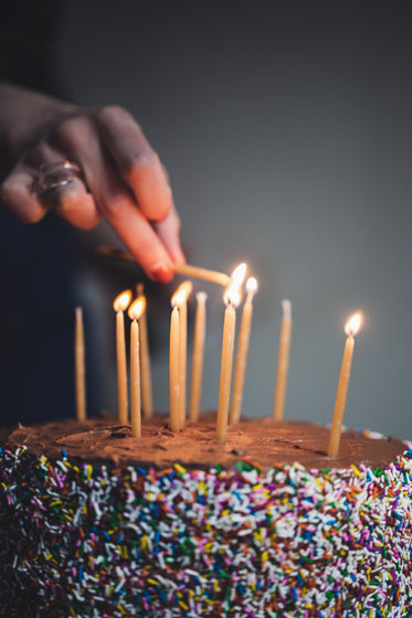 womans hand liting birthday candles