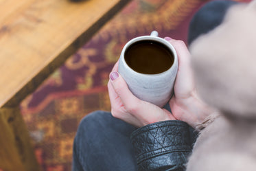 womans hands holding coffee