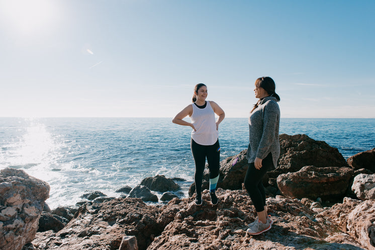 Women In Activewear Take A Moment To Share A Laugh On Beach