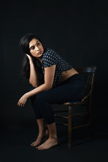 women looks away while sitting on wooden chair