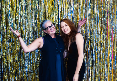 women pose in front of silver and gold metallic streamers