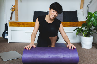 women rolls out a purple yoga mat in her living room