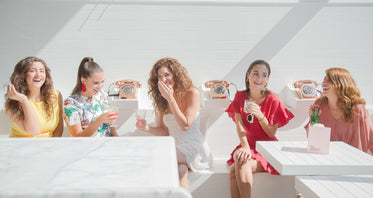 women sipping cocktails in a white room