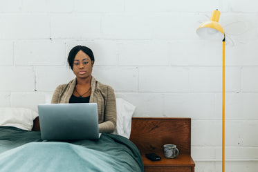 women sits in bed with laptop and coffee