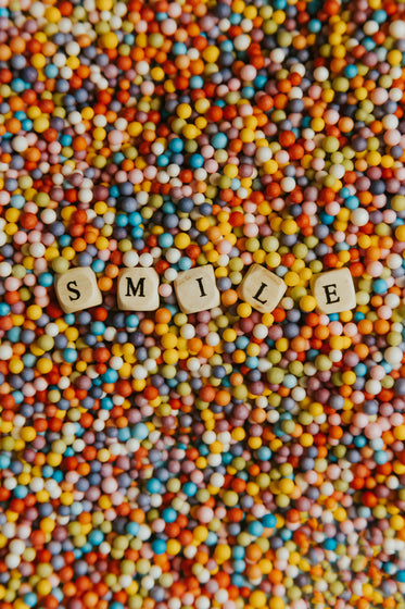 wooden block spell out smile laying on colorful dots
