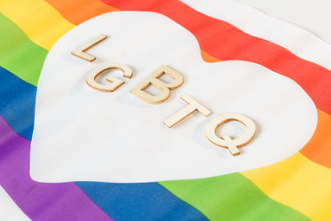 wooden lgbtq letters in heart pride flag
