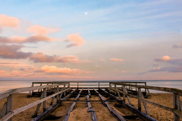wooden structure reaching to water at sunset