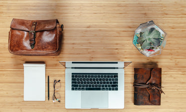 workspace flatlay with leather bag and notebook