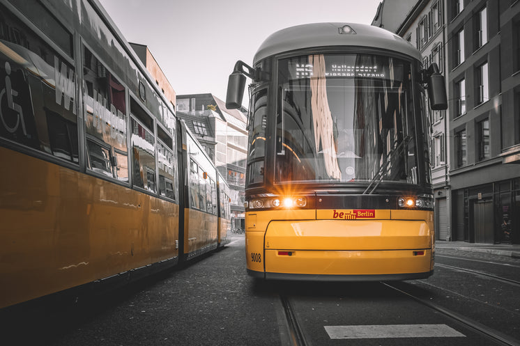 Yellow And Black Streetcar Stopped On Tracks