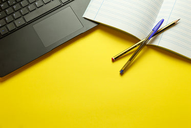 yellow table with lined notebook and computer