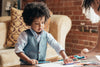 young boy drawing on coffee table