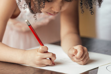young girl drawing on paper
