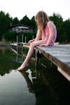young girl on dock foot in water