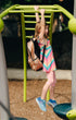 young girl swinging on bars with backpack