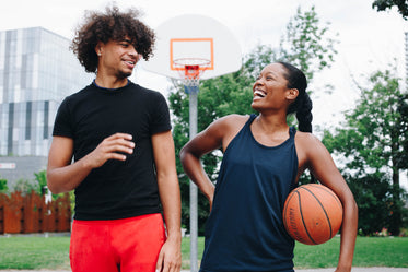 young man and woman share laugh on the court