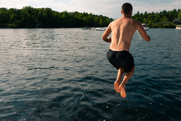 young man jumping into beautiful lake